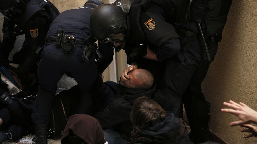 Un policía antidisturbio mete los dedos en los ojos de un activista al levantarle violentamente del suelo.