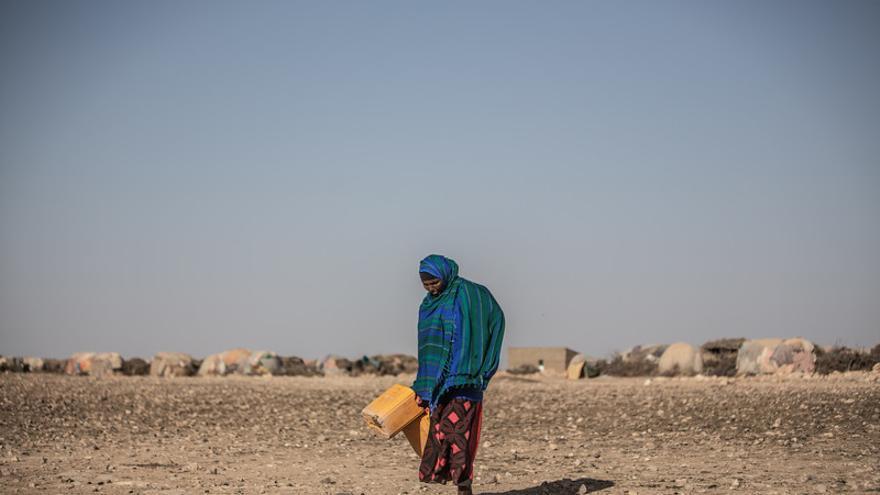 Una mujer camina cargando un bidón de agua en la Comunidad de Eilmidgan, Somalia. El cambio climático provoca que las sequías sean cada vez más recurrentes y más graves.