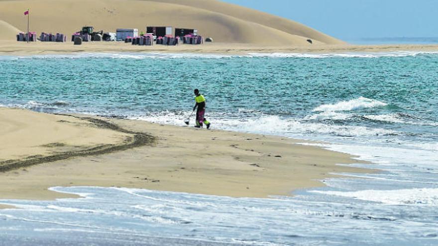 Un operario limpia la playa de Maspalomas.