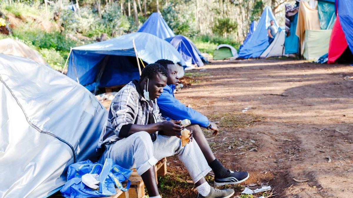 Dos migrantes comen en el exterior del campamento de Las Raíces, en Tenerife