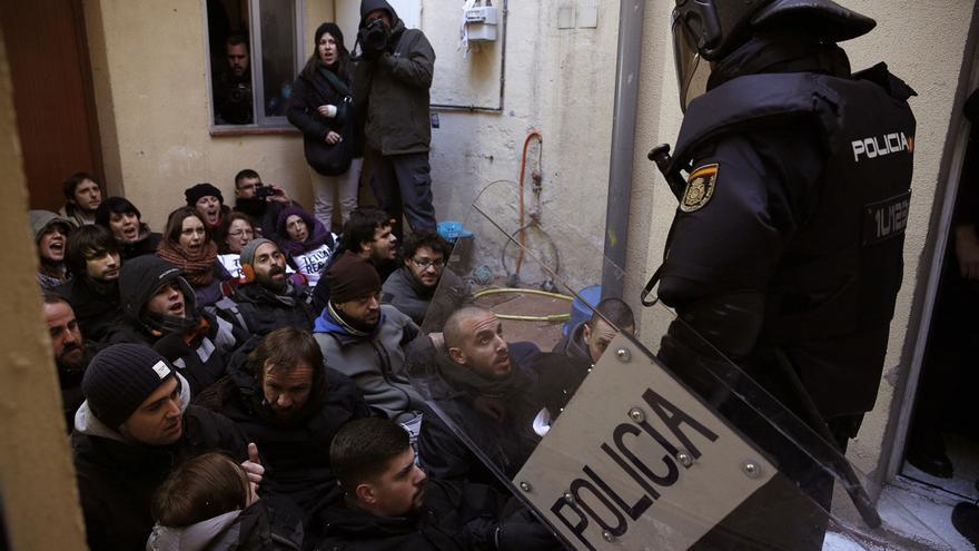 Un policía antidisturbios se dispone a sacar a los activistas que, sentados en el suelo, bloquean la puerta de entrada a la vivienda