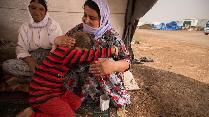 Ghasel Qassem, una yazidi de Sinjar, abraza a su hija Juaher de 7 años de edad. Los 5 miembros de su familia caminaron más de 60 km sin zapatos después de pasar siete días sitiados en el monte Sinjar. Ahora buscan refugio en el campo de refugiados de Newroz, a las afueras de Derek, Siria. Fotografía: Kira Walker.