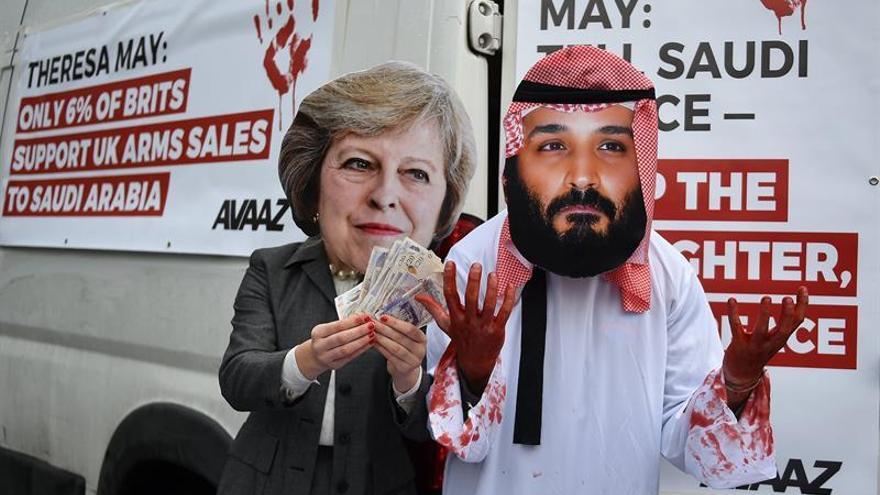 Dos activistas llevan máscaras con la imagen de la primera ministra británica, Theresa May (i), y del heredero al trono saudí