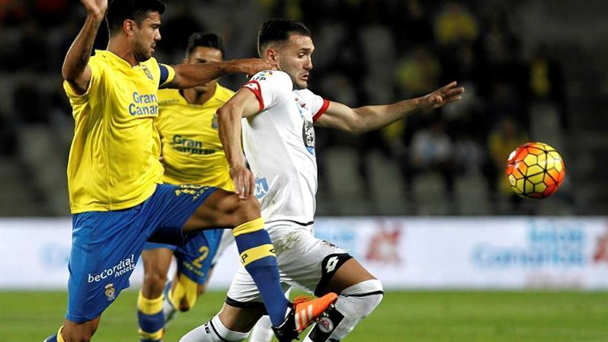 El jugador del Deportivo de La Coruña Lucas Pérez (d) trata de escapar de Aytami Artiles, de la UD Las Palmas, durante el partido de la decimotercera jornada de Liga en Primera División en el Estadio de Gran Canaria. EFE/Ángel Medina G.