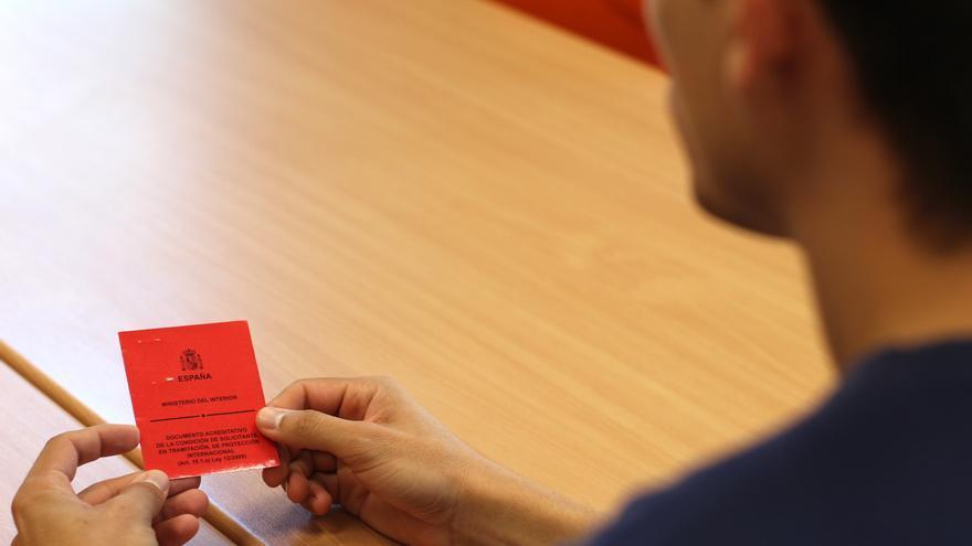 Roberto (nombre ficticio), refugiado venezolano, es asesorado en la oficina de Atención a las Personas Refugiadas de la UCM, donde acaba de empezar un master en Relaciones Internacionales. Sostiene en sus manos su 'tarjeta roja', el único documento oficial que se le entrega a los solicitantes de asilo en nuestro país | Foto: P.R.