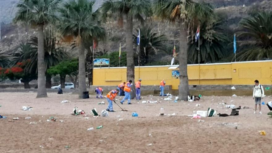 Operarios del dispositivo de limpieza en la playa de Las Teresitas las tras noche de San Juan