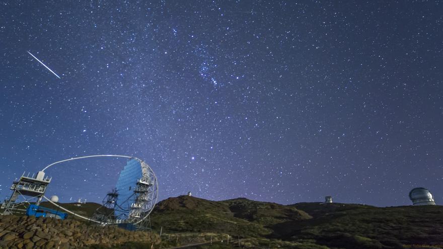 Una estrella fugaz de la lluvia de las Geménidas, captada en la madrugada de este viernes desde el Roque de Los Muchachos, cruza el cielo de La Palma.