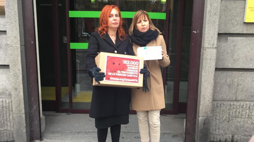 Ángeles Aguilar (izquierda), enfermera, entrega las firmas recogidas en la sede madrileña del Ministerio de Sanidad
