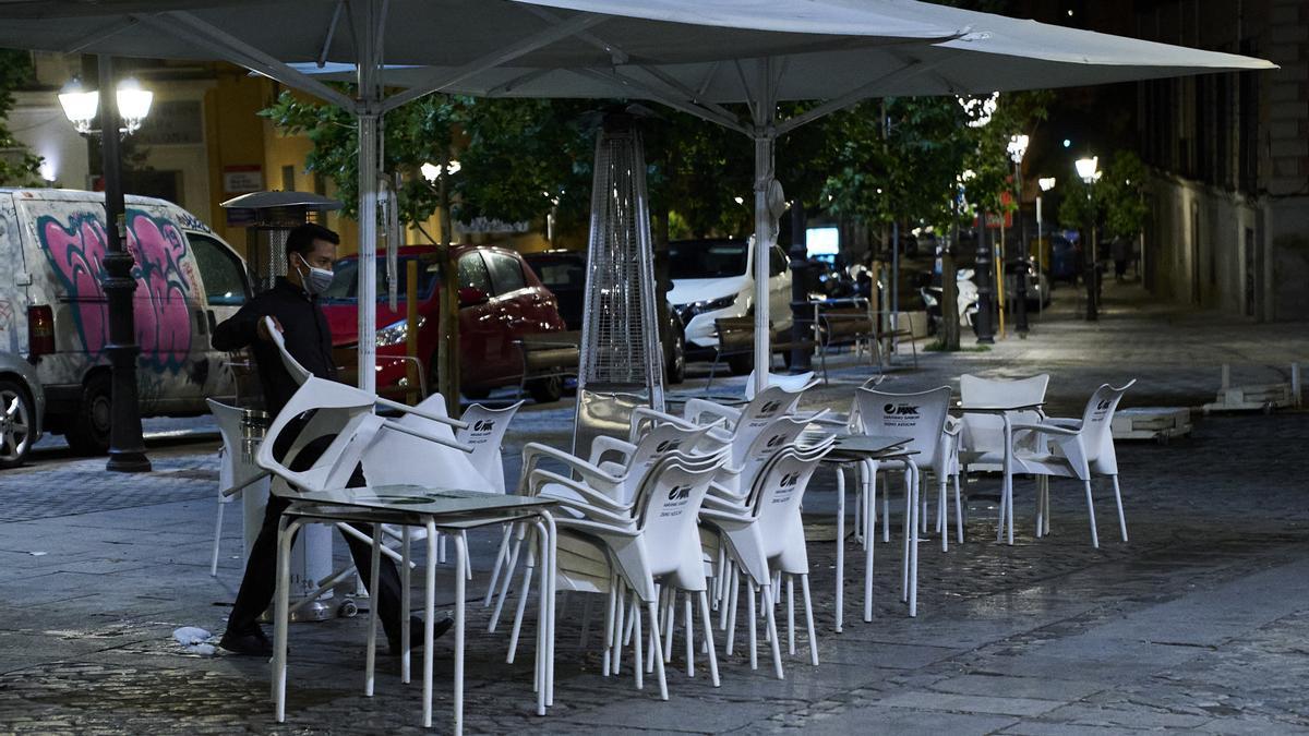Una persona recoge la terraza de una cafetería.