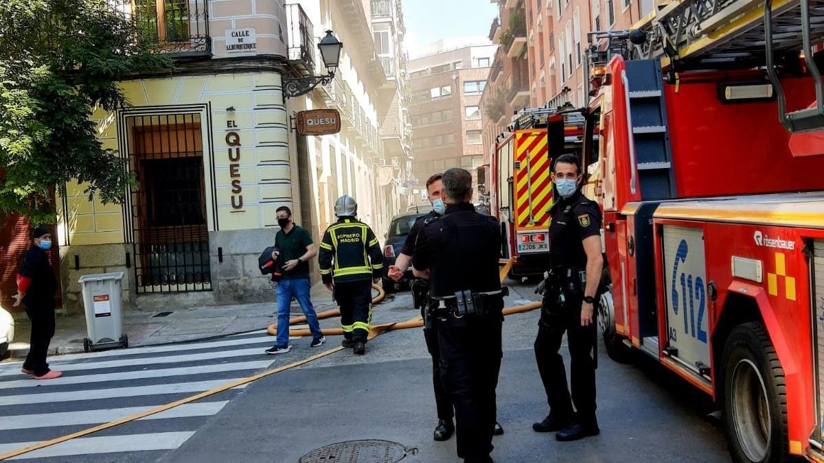Efectivos de bomberos trabajan en la extinción del humo, en la calle Alburquerque