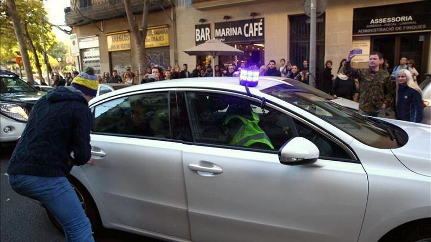 Hijo de un detenido en Barcelona intenta sacar a su padre del coche policial