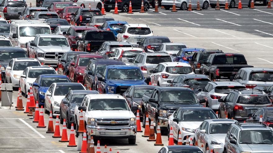 Cientos de carros con personas hacen fila para someterse a la prueba del coronavirus por parte de miembros de la Guardia Nacional del Ejército de Florida, en el estacionamiento del Hard Rock Stadium en Miami, Florida (EE.UU.), este 30 de junio de 2020.