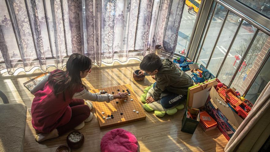 Michael (D) juega con su hermana Elaine (I) en su casa mientras las escuelas siguen cerradas tras el brote del nuevo coronavirus, en Pekín, China, el 19 de febrero de 2020