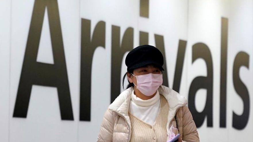 A passenger arrives wearing a mask at Terminal 4, Heathrow Airport, London, Britain, 22 January 2020. Britain will monitor flights arriving from China as a precautionary measure after the spread of a new coronavirus.
