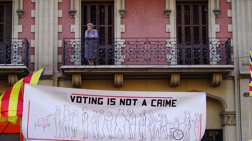 """Una vecina observa la marcha mientras pasa un cartel donde se lee que """"votar no es un delito"""""""