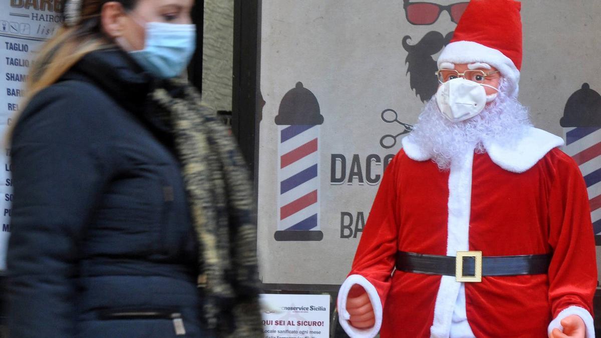 Un Papá Noel con mascarilla en las calles de Palermo, Italia