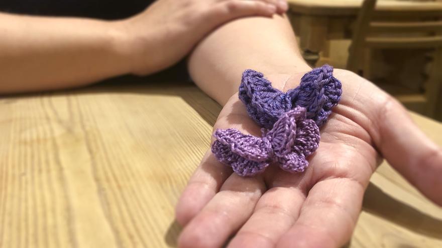 Itziar Prats sosteniendo dos de las mariposas que ha tejido. Una grande, Nerea, y una pequeña, Martina.