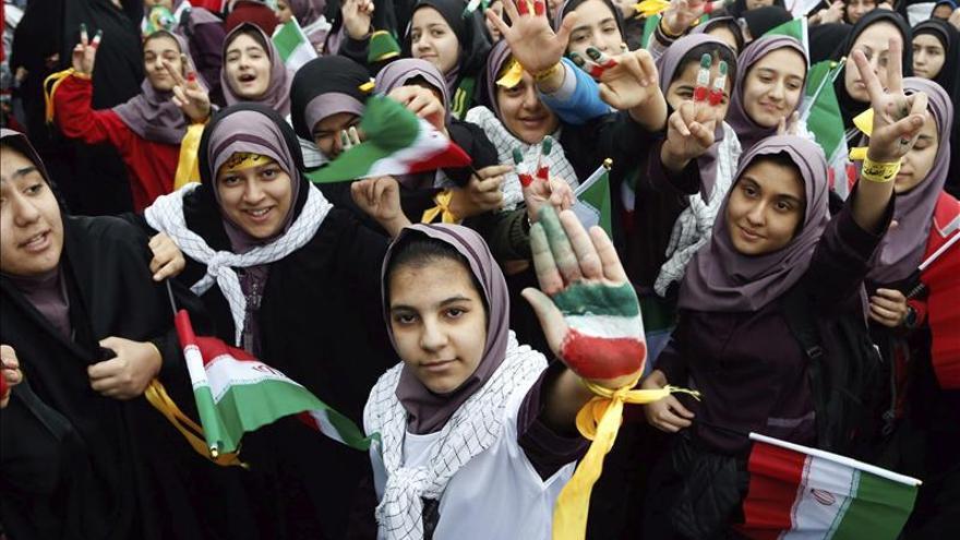 Jóvenes iraníes muestran sus manos pintada con los colores de la bandera de su país durante una ceremonia conmemorativa por el 36 aniversario de la victoria de la Revolución Islámica.