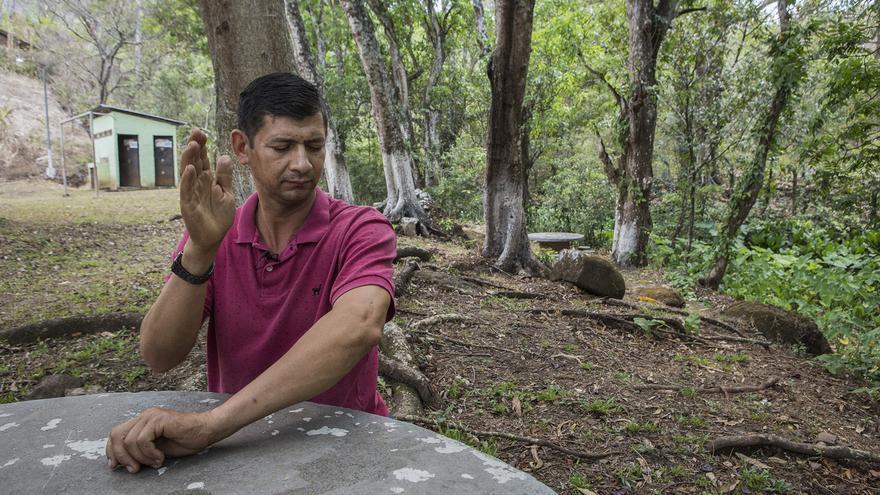 Saúl trata de cazar un mosquito mientras es entrevistado después de tener una reunión con varios migrantes en Carasque