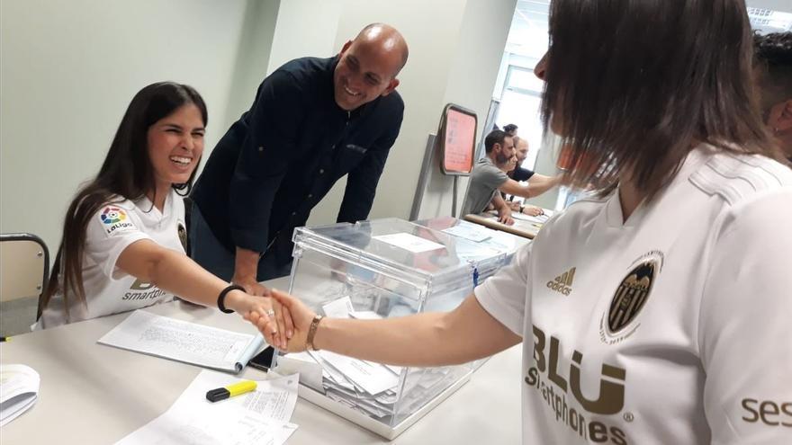 Una votante saluda a la presidenta de la mesa, ambas con la camiseta del Valencia CF
