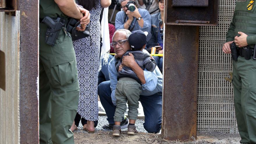 Una familia mexicana se abraza en la frontera mientras dos agentes fronterizos observan / Earnie Grafton