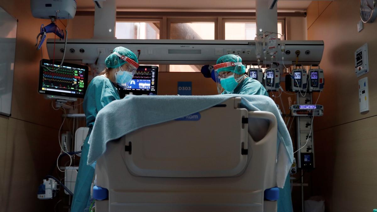 Dos profesionales sanitarios trabajan en la UCI de un hospital.