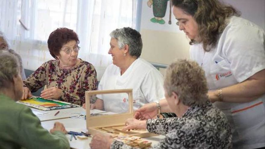 Auxiliares conversan con mujeres mayores en una residencia de Suara. FOTOGRAFÍA: ANDREA BOSCH