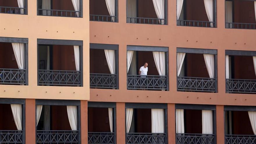 Un turista se asoma desde el balcón de su habitación en el hotel del sur de Tenerife, que permanece aislado tras detectarse cuatro casos de coronavirus de Wuhan.