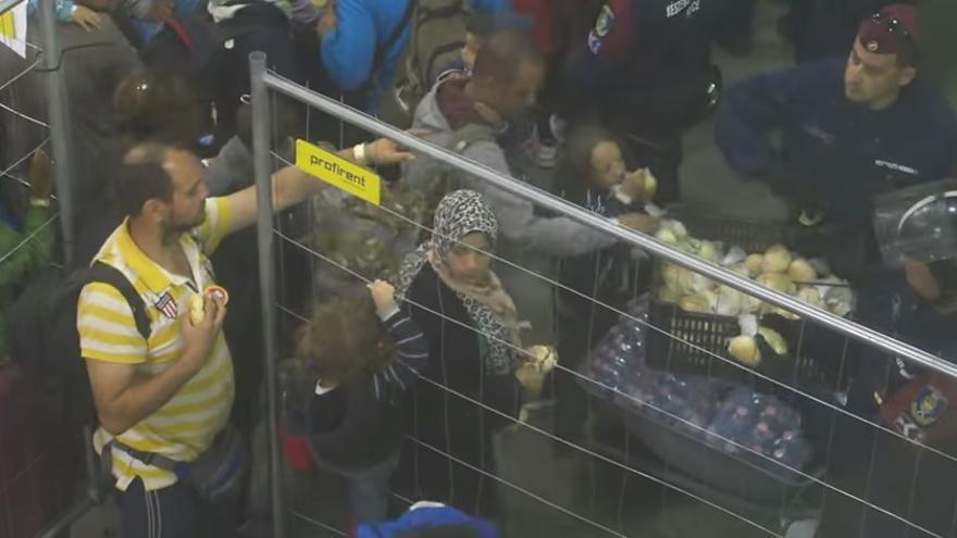 Niños y adultos se aferran a las verjas y llaman la atención de los policías para conseguir las bolsas de comida. / Captura del vídeo de Michaela Spritzendorfer.