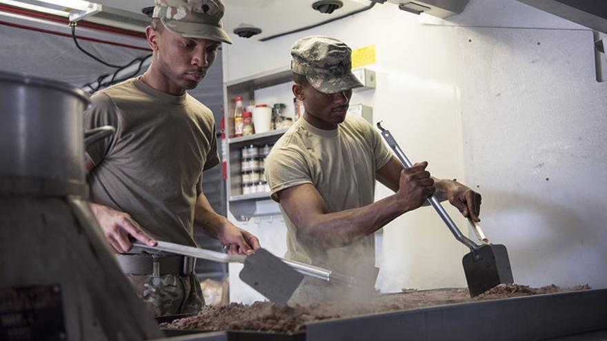 Dos soldados estadounidenses preparan la comida para sus colegas en Indiana.