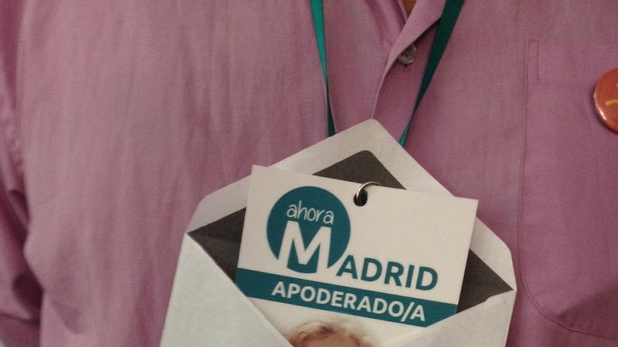 Un apoderado de Ahora Madrid tapa la foto de Manuela Carmena de la acreditación con un sobre. / eldiario.es