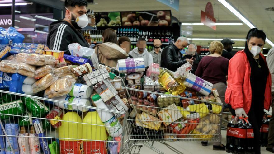 Decenas de personas cargadas con provisiones esperan para poder pagar en un supermercado en Madrid.