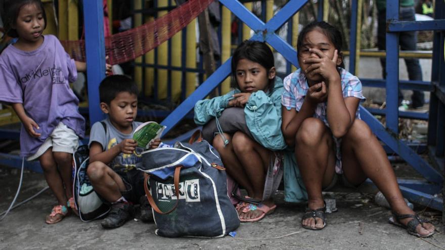Un grupo de niños filipinos, víctimas evacuadas del tifón Yolanda, esperan en las proximidades del aeropuerto de Tacloban el 13 de noviembre de 2013./ Fotografía: Acción contra el Hambre/Daniel Burgui