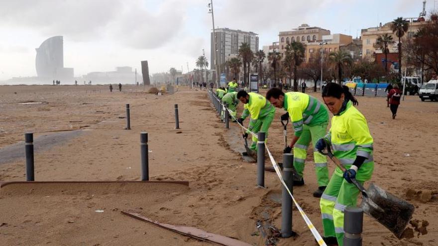 Trabajadores de la limpieza realizan su trabajo este jueves en la playa de la Barceloneta, gravemente afectada por la borrasca Gloria, que se ha cebado especialmente con el frente marítimo de Barcelona.