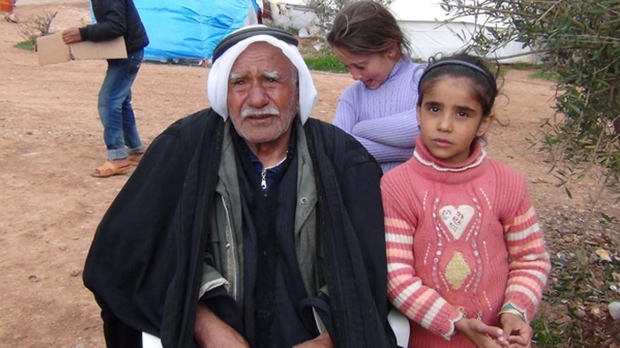 Un anciano y sus nietos, fotografiados en un campamento para personas desplazadas en Atmeh, al norte de Siria, febrero 2013 © AI