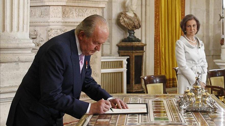 El rey firma la ley de abdicación en el Salón de Columna del Palacio Real.