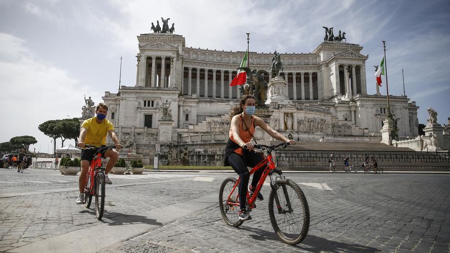 Dos personas montando en bicicleta en la plaza de Venecia en Roma (Italia).