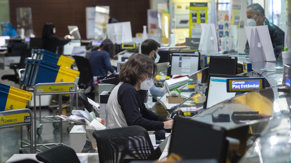 Varios empleados trabajan en la Oficina de Correos de Cibeles, en Madrid.