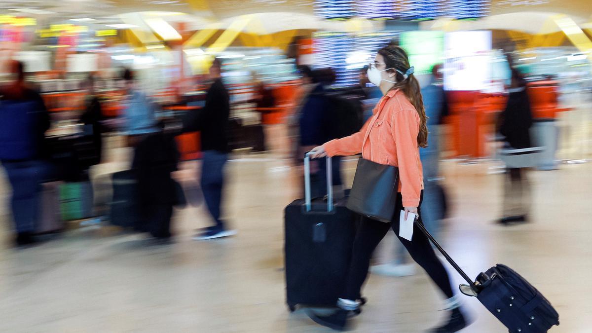 Viajeros protegidos con mascarillas en el aeropuerto Adolfo Suárez Madrid Barajas.