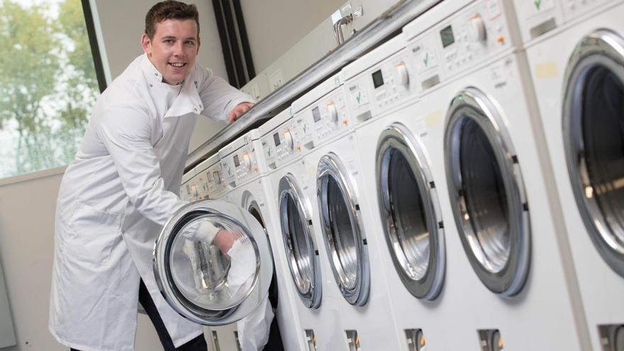 Max Kelly posa junto a unas lavadoras.