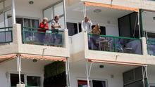 Varios turistas conversan desde sus balcones en Los Cristianos debido a las restricciones por el estado de alarma. EFE/Ramón de la Rocha