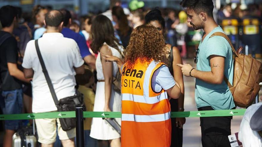 Una trabajadora de Aena orienta a un viajero durante una huelga en El Prat