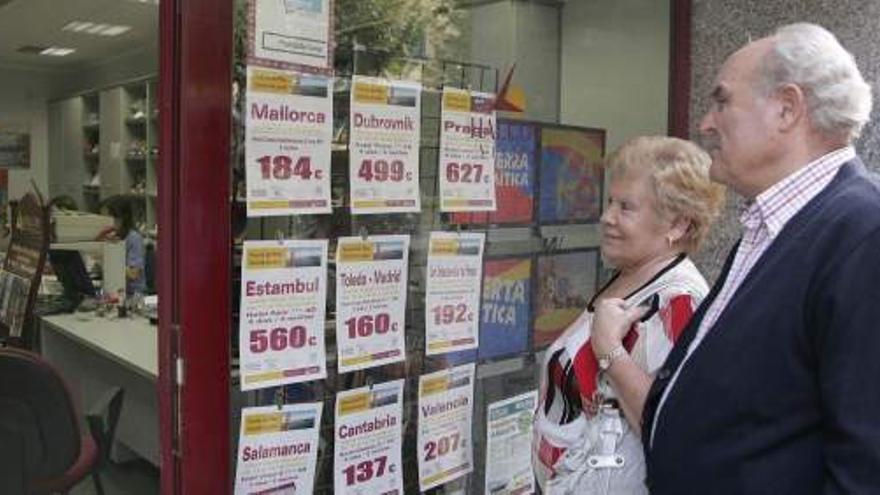 Pareja de pensionistas frente a ofertas de viaje del Imserso