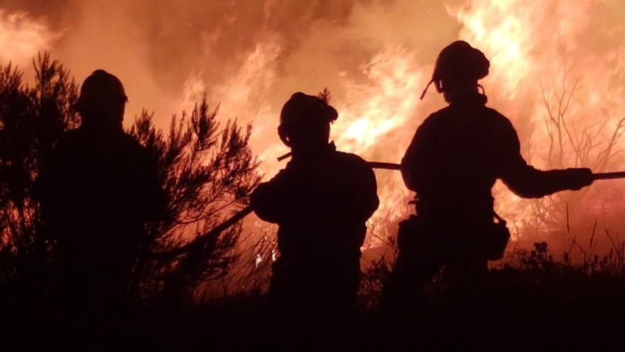 Bomberos forestales trabajan en un incendio en Parada de Sil, a mediodía de este lunes