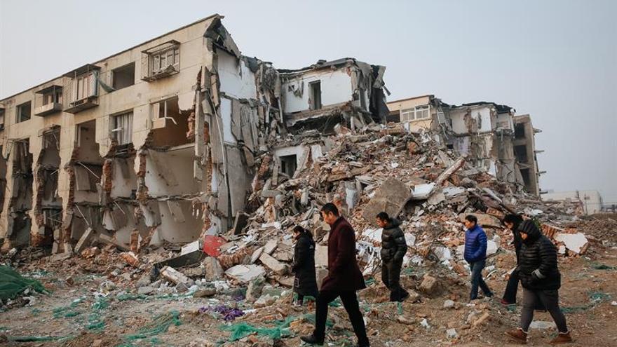 Un grupo de personas que fueron desalojadas, caminando junto a unos edificios demolidos, en las afueras de Pekín (China).