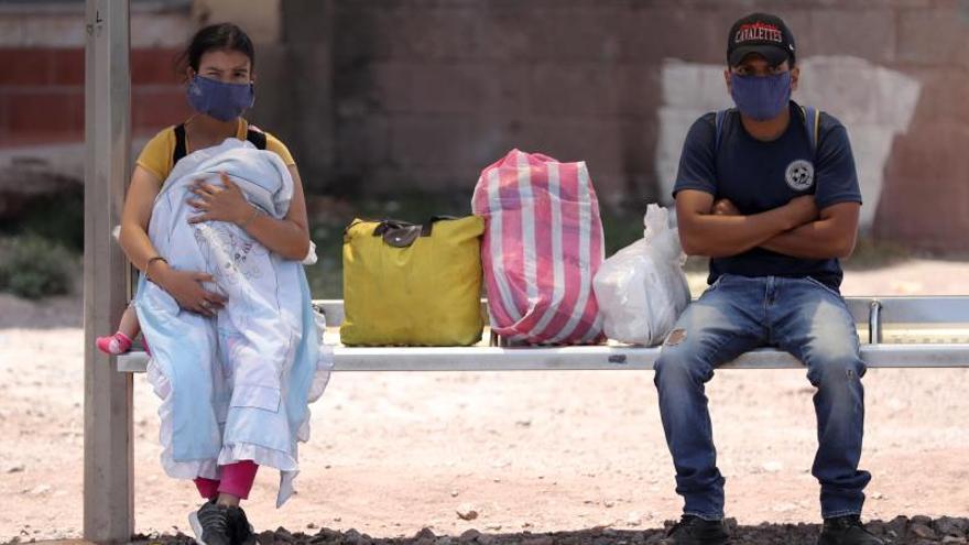 Dos personas esperan en un paradero de autobuses, en Tegucigalpa (Honduras).