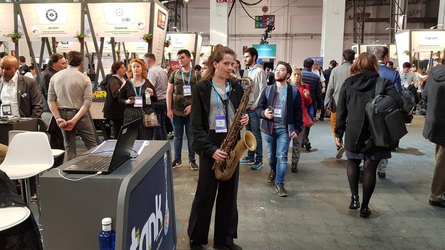 Una asistente a la sexta edición del 4 Years From Now (4YFN) toca el saxofón al lado de un stand de la feria