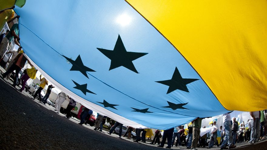 Manifestantes despliegan una bandera con las siete estrellas verdes.