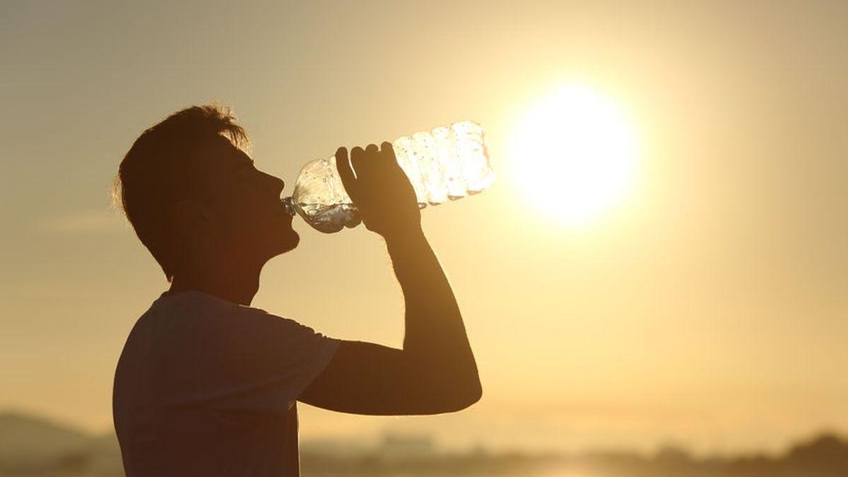 Imagen de archivo de un hombre bebiendo agua durante una ola de calor