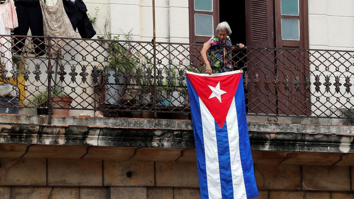 Una mujer sale al balcón donde se expone una bandera cubana en La Habana, Cuba.